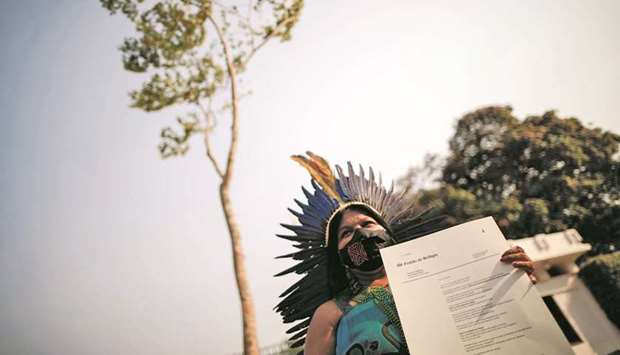 Indigenous leader Sonia Guajajara poses for a photo with a manifest letter in front of a Jatoba tree