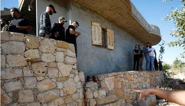 People check the scene where three Palestinians were killed by Israeli forces during a raid, in Beit