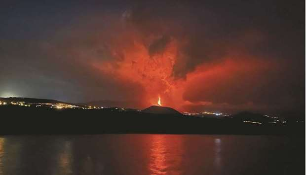 Lava and smoke rise from an erupting volcano in the Cumbre Vieja national park at Tazacorte, on the