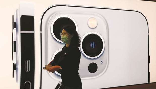 An Apple employee wearing a face mask walks past an image of an iPhone 13 Pro at an Apple Store in B