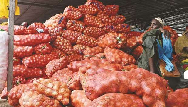 An onion farmer sits on his produce at the Notto Gouye Diama market, one of the main markets for agr