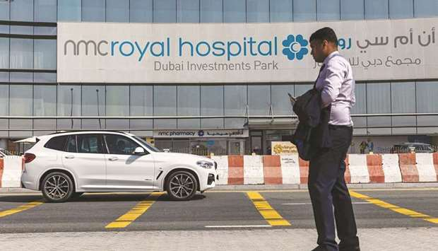 A pedestrian waits outside the entrance to the NMC Royal Hospital, operated by NMC Health, in Dubai