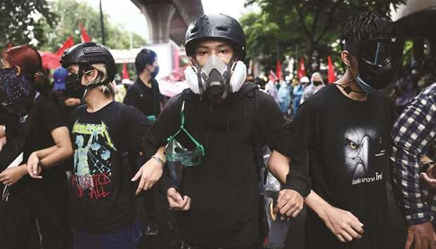 Anti-government protesters wearing protective gear take part in a demonstration in Bangkok.