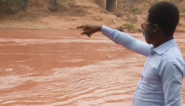 A man gestures as he looks at the Tshikapa river after it turned red, in Tshikapa City, Kasai Provin