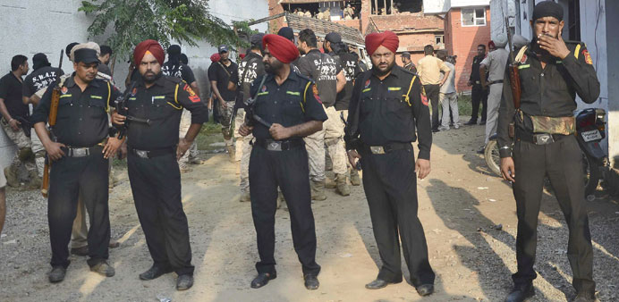 Security personnel stand at the site of a gunfight in Dinanagar town in Gurdaspur.