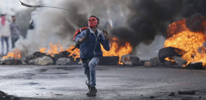 A Palestinian protester uses a sling to hurl stones towards Israeli troops near the Jewish settlemen