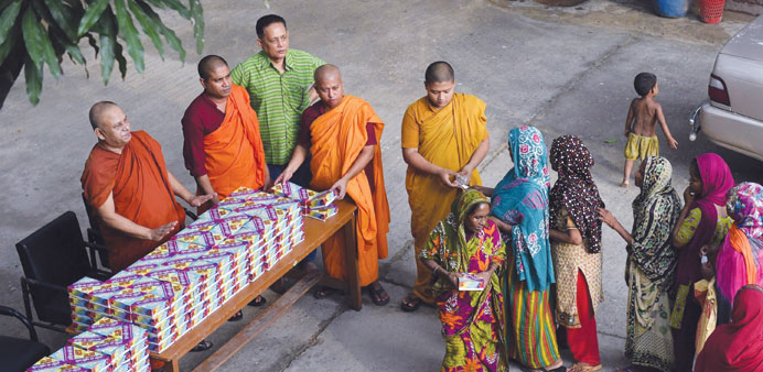 Buddhist monks giving out Iftar meals to Bangladeshi Muslims in the main shrine of Dhammarajika Mona
