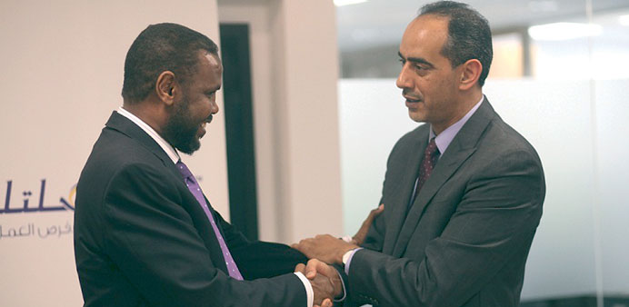 Officials of Silatech and Kaah Express shake hands after signing an agreement.