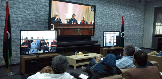 Journalists watch screens broadcasting the trial of Saif al-Islam Gaddafi (screen on right) and form