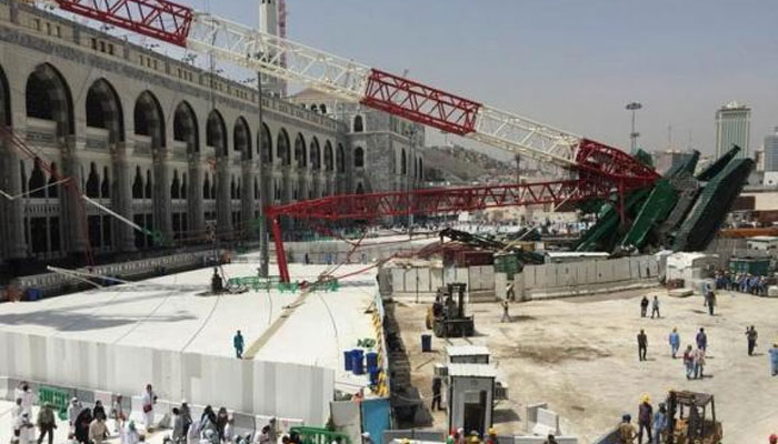 Pilgrims walk past a collapsed crane that killed 107 people at the Grand Mosque in Mecca, Saudi Arab