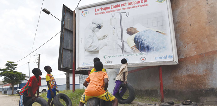 Boys look at a poster warning of the dangers of the Ebola virus, reading 'the risk Ebola is still th