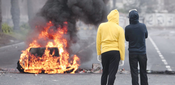 Demonstrators standing near a burning garbage container in the village of Sanabis, west of Manama, y