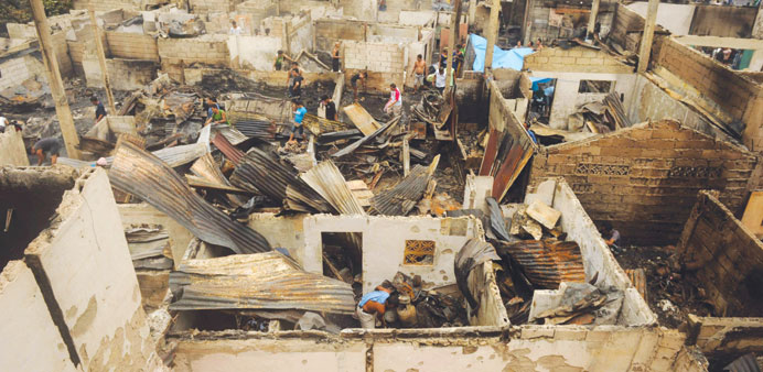 Residents search for salvageable materials among debris after an overnight fire razed a slum area