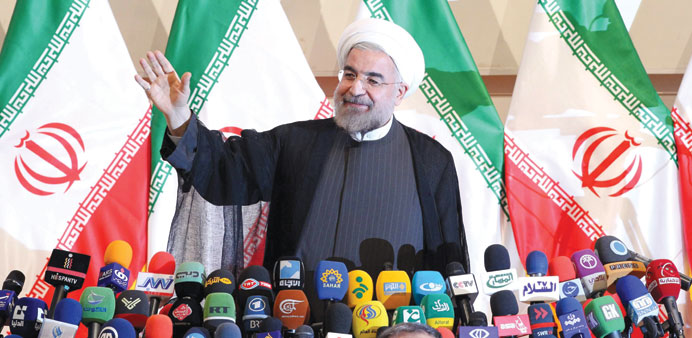 Rohani waves to the media during the press conference in Tehran yesterday.