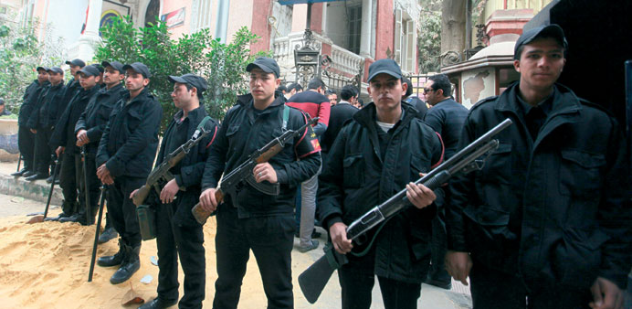 Egyptian policemen guard a police station during a strike in Cairo yesterday.
