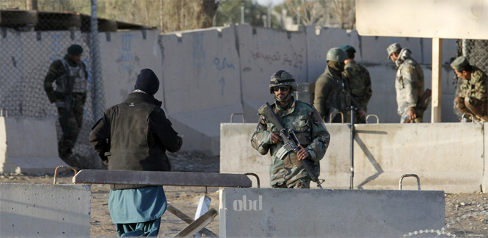 Afghan security forces stand guard at the entrance gate of Kandahar Airport