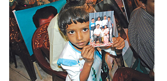 A girl holds a picture of relatives missing from Sri Lanka's 26-year long civil war during a meeting
