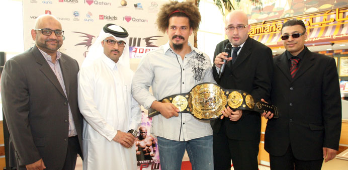 Carlito (middle), flanked by the organisers, with the title belt yesterday.