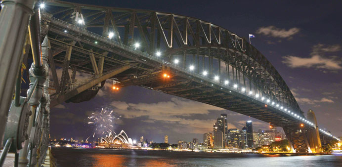 Fireworks fade as lights go out on the Sydney Harbour Bridge and Opera House to signal the start of