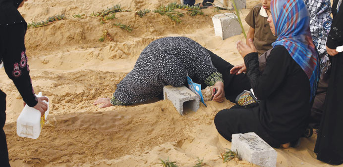 A Palestinian woman crying at the grave of her son who was killed during the Israeli attack, at a ce
