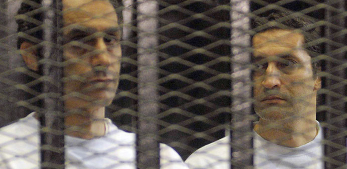 A file picture taken on June 2, 2012, shows Alaa and Gamal Mubarak standing inside a cage in a court