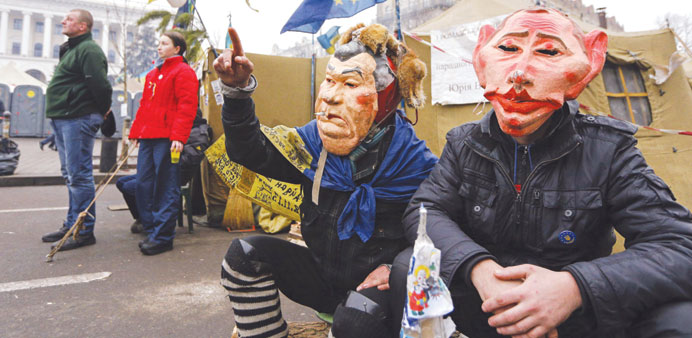 Protesters wearing masks depicting Ukrainian President Viktor Yanukovych and Russian President Vladi