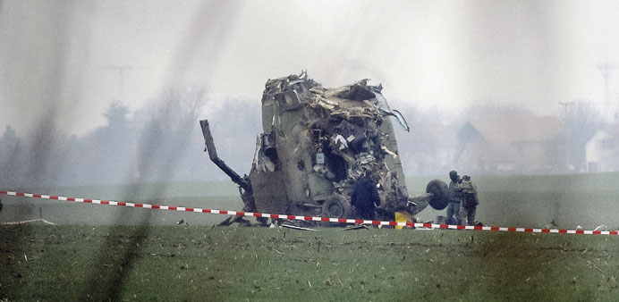 Army soldiers stand next to the wreckage of the Serbian Mi-17 type military helicopter that crashed