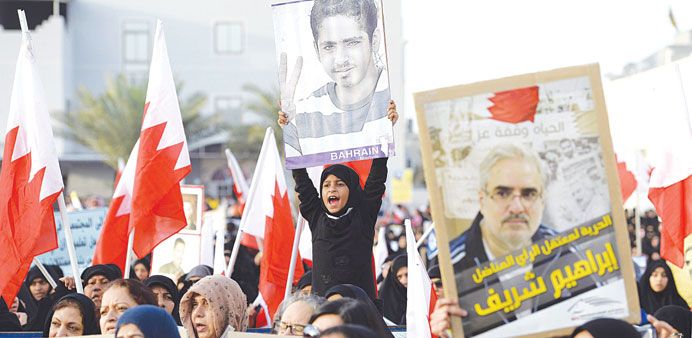 A girl holds a photo of a detained relative during a sit-in in Sar village, north of Manama, yesterd