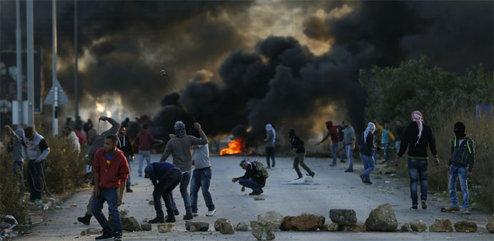 Palestinian protesters throw stones towards Israeli security forces during clashes