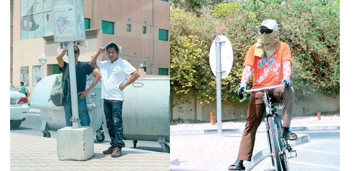 Two expatriates waiting for public transport at a bus stop a little after noon yesterday. Right: A c
