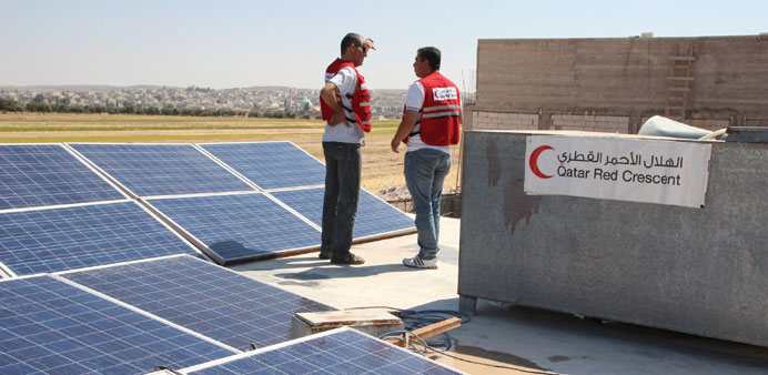 QRCS staff install 30 solar panels on top of the water well.