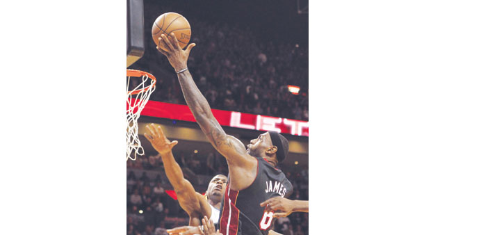 Miami Heat forward LeBron James (R) scores the winning basket in the final seconds of their NBA bask