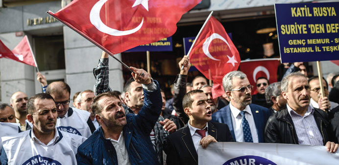 A protester waves Turkey's national flag while others shout slogans in front of the Russian consulat