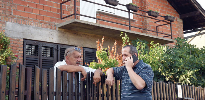 Friends of Salopek stand outside his home in Vrpolje, eastern Croatia, on Friday.