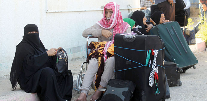 Palestinians gather at the Rafah border crossing in the southern Gaza Strip, as they await permissio