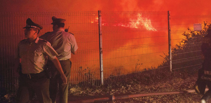 Police officers stand by while a forest fire burns the hills of Valparaiso city, northwest of Santia