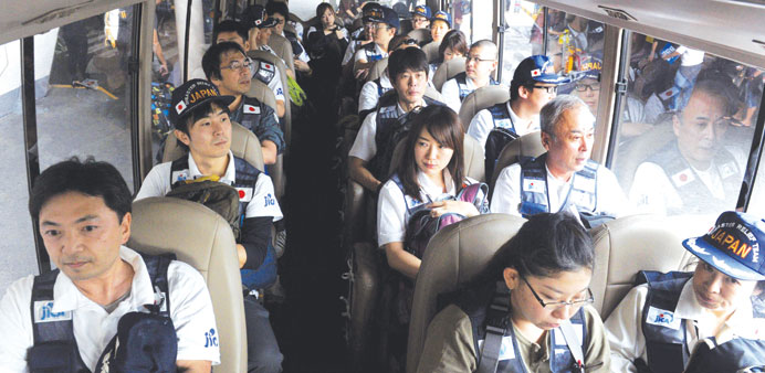 Members of the Japan Disaster Relief Team ride onboard a bus as they arrive at Manila's Internationa