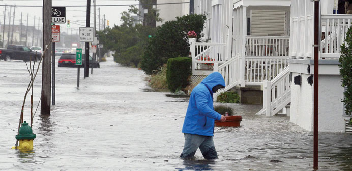 A man walks through knee-deep water along a flooded West Avenue in Ocean City, New Jersey, on Friday