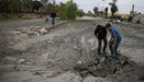 Boys inspect a hole in the ground after an airstrike near a playground in Douma