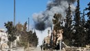 Opposition fighters backing Turkish troops gather on a road as smoke billows following an air strike