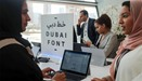 """Attendees look at computers showing the """"Dubai Font"""", the first typeface developed by Microsoft for"""